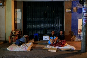 People sit on a makeshift bed on a Maicao street where Venezuelan immigrants gather to spend the night.