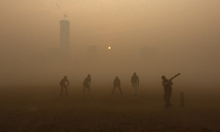 Boys play cricket in a public park amidst heavy fog on a cold winter morning in Kolkata, India