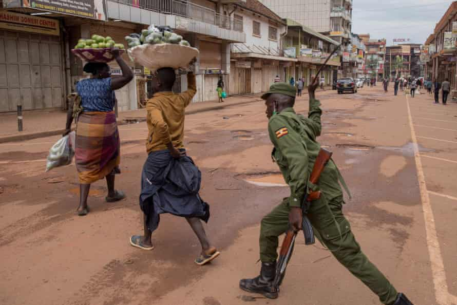 A police officer beats a female orange vendor on a street in Kampala, Uganda, on 26 March 2020