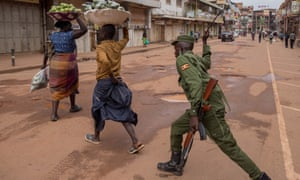 An armed policeman chases fruit vendors off the streets of Kampala