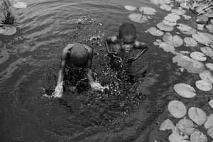 School children, aged 8 and 9, wash in a river in Nampula province