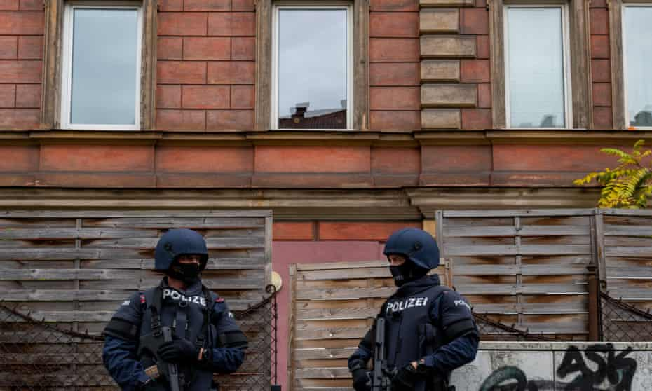 Police officers stand in front of a building in Linz, Austria, where a man was detained in connection with the Vienna shooting.