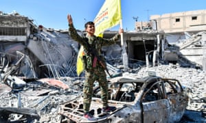 An SDF fighter celebrates wrapping up a more than four-month offensive against what used to be the inner sanctum of Islamic State's self-proclaimed caliphate