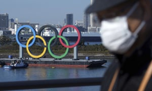 A man wearing a face mask with the Olympic rings in the background in Tokyo