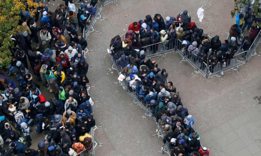 Migrants queue outside Office of Health and Social Affairs as they wait to register.