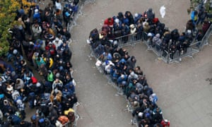 Migrants queue outside Office of Health and Social Affairs as they wait to register in Berlin.