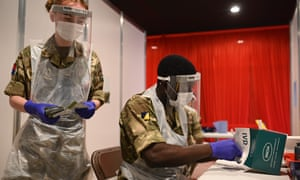 British soldiers process and record coronavirus tests inside Anfield Stadium in Liverpool.