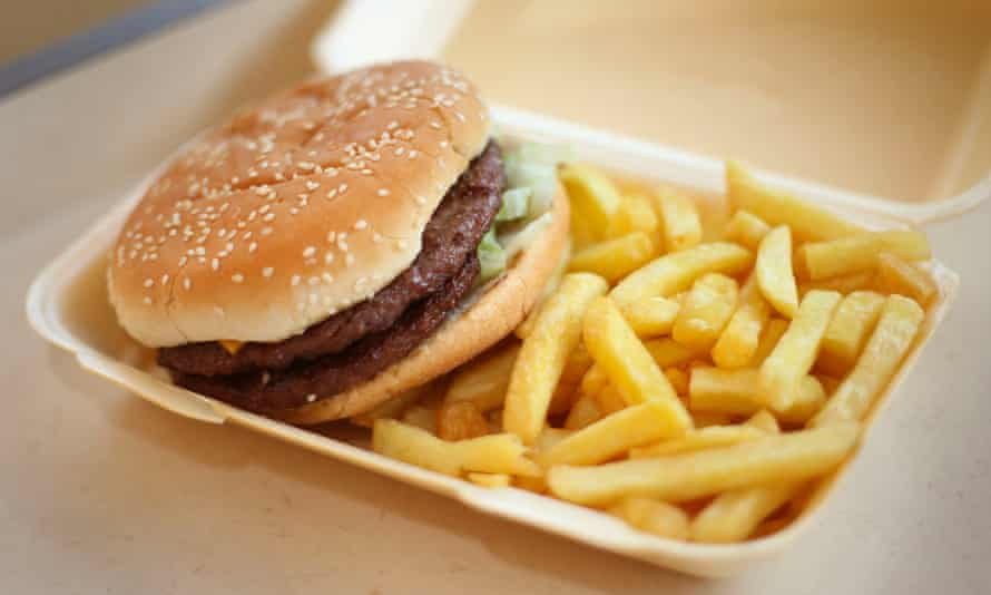A burger and chips in a takeaway carton