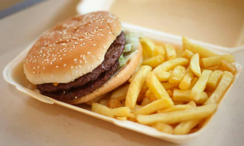A half-pounder burger and chips in a takeaway carton