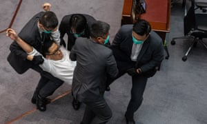A pro-democracy lawmaker is carried out of the chamber by security guards during a scuffle with pro-Beijing lawmakers at a the legislative council meeting in Hong Kong