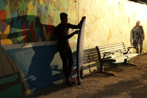 A surfer waits for the 7am reopening of Bondi beach