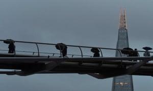 City workers cross the Millennium footbridge in London