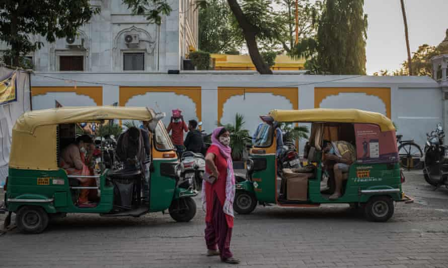 People receive oxygen while sitting in auto rickshaws at a makeshift clinic in Delhi