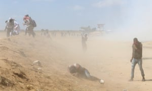 Palestinian demonstrators react to teargas fired by Israeli forces during a protest marking the 70th anniversary of Nakba, at the Israel-Gaza border in the southern Gaza Strip