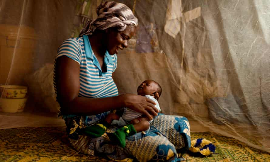 A mother in Burkin a Faso, where trials involving 450 children were held, protects her baby behind a mosquito net
