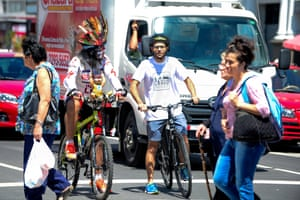 The founder of cycling group Chepecletas, Roberto Guzman, right, waits at a stop light during a bike tour through San José for World Car Free Day.