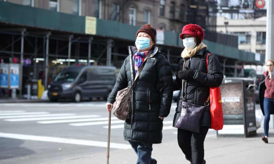 People wear medical masks as a precaution against coronavirus, walking around the in the streets of New York on Friday.