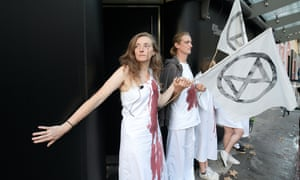 Extinction Rebellion protesters take part in 'die-in' outside London fashion week's headquarters.