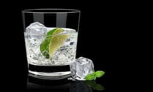 A glass of drink with ice and lime