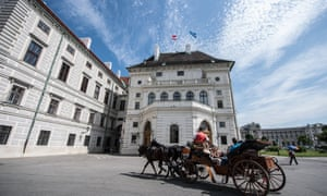 A horse-drawn carriage drives by the Hofburg palace in Vienna, part of the world heritage site in the city.