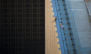 Two men sitting on a ledge in Hong Kong take a series of selfies as part of a craze known as rooftopping