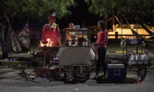 Venezuelan migrants run a street food stall at a bus terminal in Maicao, La Guajira, in northern Colombia