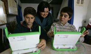 """** TO GO WITH HUNDRED DOLLAR LAPTOP  ** Brothers Franco and Lucas Scalabrino, right, show to their mother, Maria Fojo, their new """"hundred-dollar"""" laptop computers given them days earlier by the One Laptop Per Child project in Villa Cardal, Uruguay, Wednesday, May 16, 2007.  The ambitious nonprofit project was launched in 2005 by the director of the media lab at the Massachusetts Institute of Technology, Nicholas Negroponte. The program aims to bring information technology to children in developing countries by building low-cost laptops. (AP Photo/Marcelo Hernandez)"""