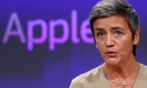 The EU's competition commissioner Margrethe Vestager, with the word Apple projected onto the background