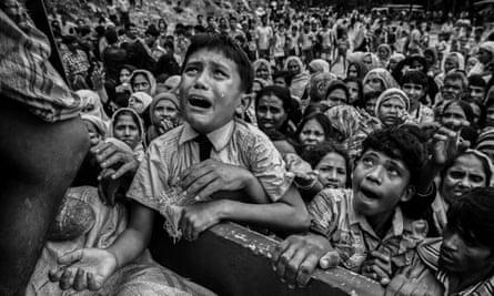 A Rohingya refugee boy cries as he climbs on a truck distributing aid for a local NGO near the Balukali refugee camp in Cox's Bazar, Bangladesh.