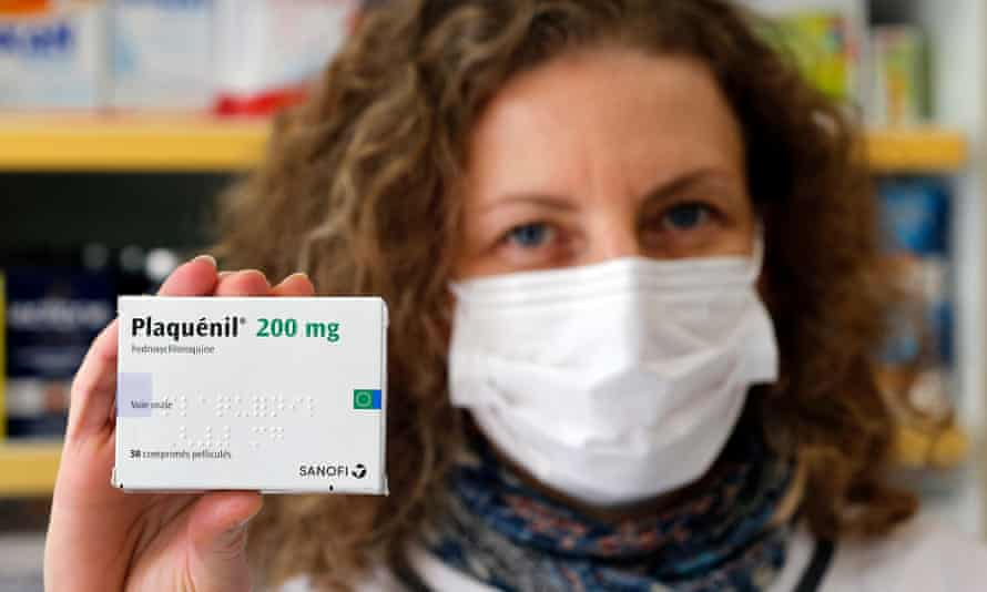 A French pharmacy employee holds up a pack of Plaquénil, the brand name for chloroquine. There are hopes the malaria treatment could help fight Covid-19.