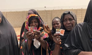 Women show photographs of relatives that have disappeared after being arrested by Nigeria's military