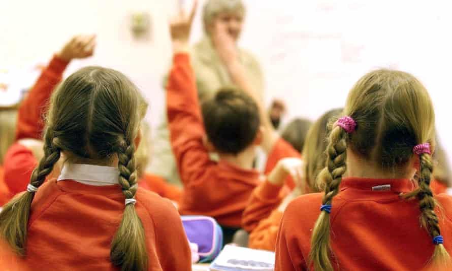 Backs of heads of schoolchildren in class wearing red sweaters