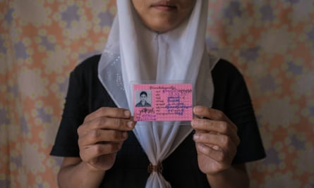"""A young Muslim girls holds her identity card stating that her race is """"Burmese Indian""""."""