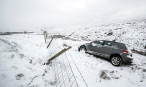 A car abandoned in heavy snow on Snake Pass in the Peak District
