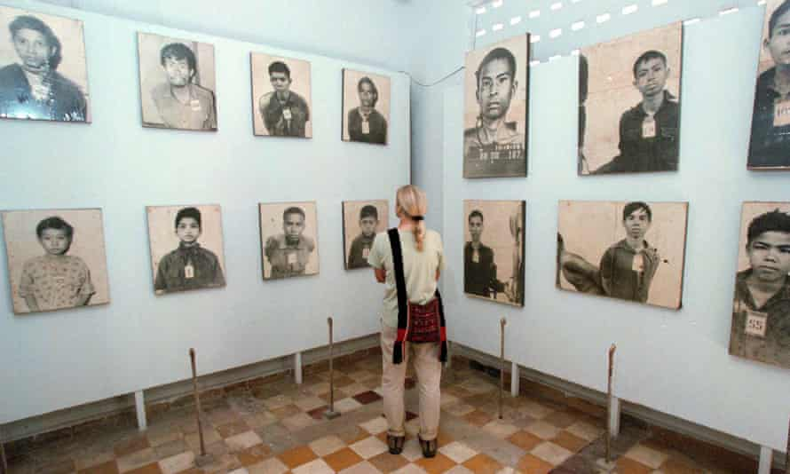A tourist looks at portraits of Khmer Rouge victims on display at the Tuol Sleng Genocide Museum in Phnom Penh, Cambodia.