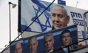 A Likud party election campaign billboard with an image of Benjamin Netanyahu is seen above a billboard featuring Benny Gantz, leader of Blue and White party, in Petah Tikva, Israel.