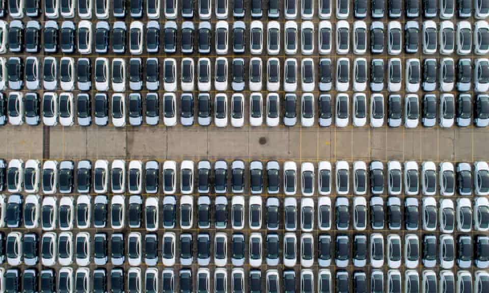 an overhead shot of a huge number of new cars parked in rows