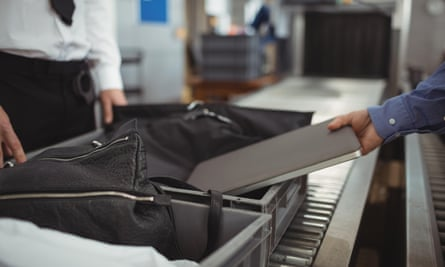 A passenger puts a laptop into a tray for an airport security check.