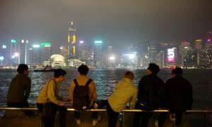 People with smoggy Hong Kong skyline