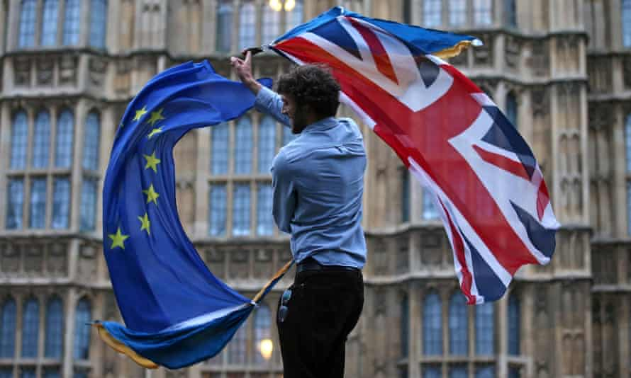 A man waving both a union jack and a European flag outside parliament in London.
