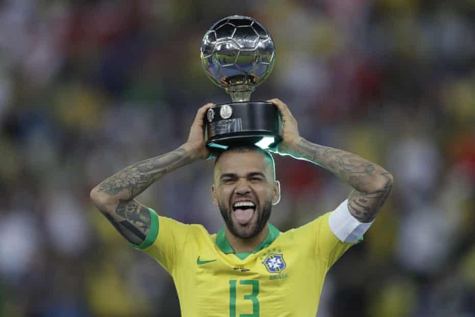 Dani Alves celebrates with his Copa América player of the tournament award.
