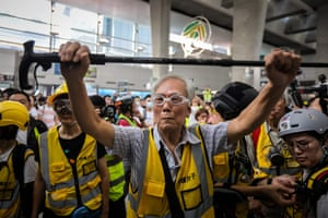 """This picture taken on September 7, 2019 shows """"Grandpa Wong"""", 85, shielding protesters from the police by holding his walking stick up along with other """"silver hair"""" volunteers in the Tung Chung district in Hong Kong. - Despite his age, Wong is a regular sight at Hong Kong's street battles, hobbling towards police lines, placing himself in between riot officers and hardcore protesters, hoping to de-escalate what have now become near daily clashes."""