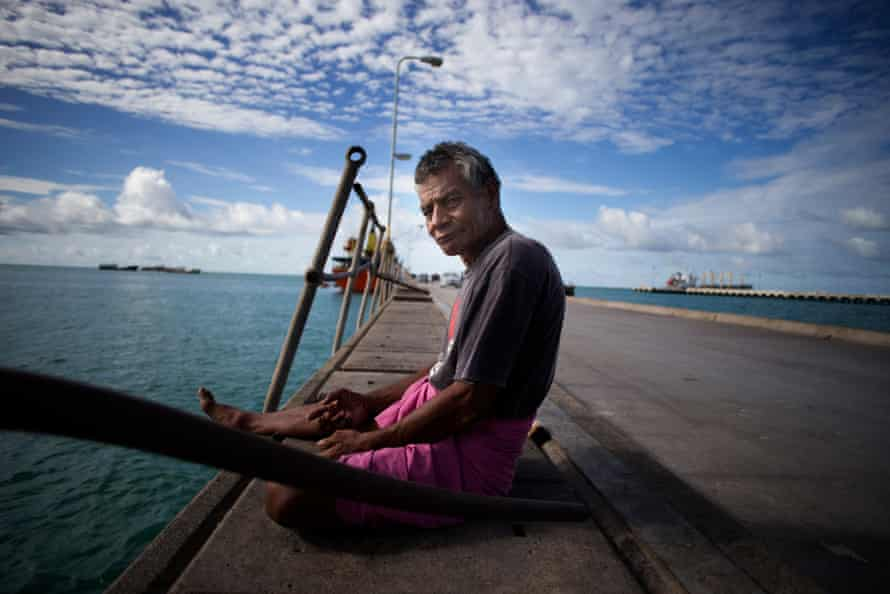 A man fishes off the main wharf at Betio.
