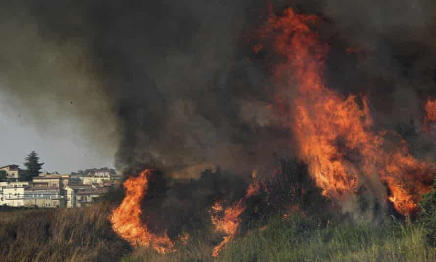 A view of a fire in the Municipality of Blufi, in the upper Madonie, near Palermo, Sicily, Italy, as many wildfires continue plaguing the region. Sicily, Sardinia, Calabria and also central Italy, where temperatures are expected to reach record hights, were badly hit by wildfires. Climate scientists say there is little doubt that climate change from the burning of coal, oil and natural gas is driving extreme events, such as heat waves, droughts, wildfires, floods and storms. (AP Photo/Salvatore Cavalli)