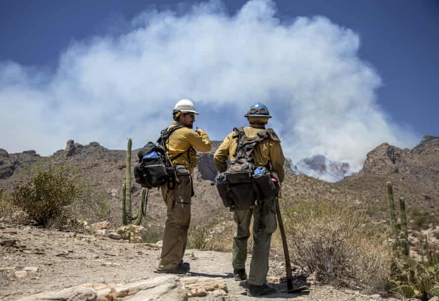 In June, firefighters talk near the Finger Rock Canyon trailhead as smoke billows from the Bighorn Fire in the distance, in Tucson, Arizona.
