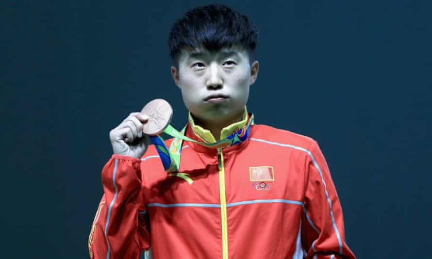 Disappointed bronze medalist Yuehong Li of China poses on the podium during the medal ceremony for the Men's rapid fire pistol event.