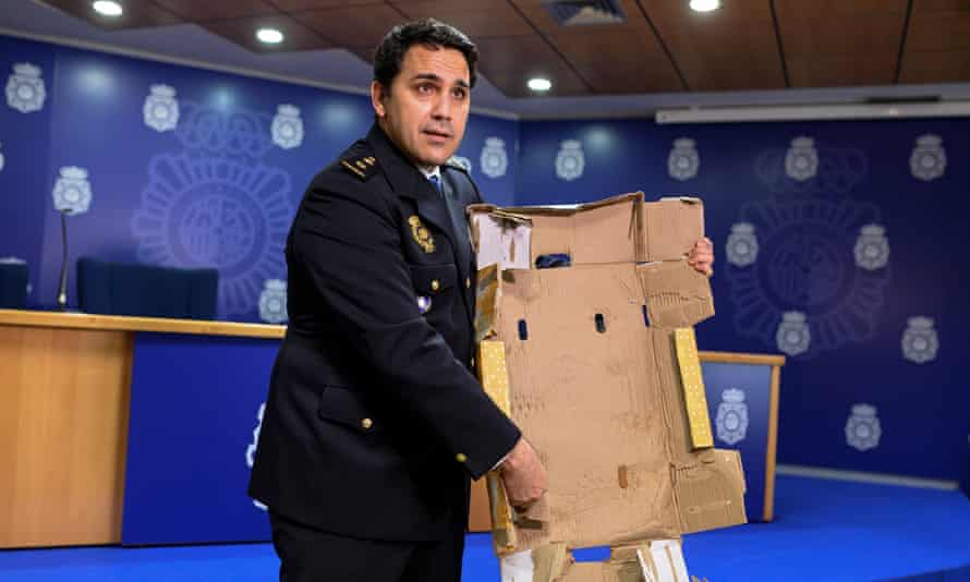 A Spanish police inspector displays a cocaine-impregnated fruit box at a press conference in Madrid