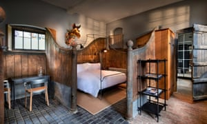 A double bed with white bedding in an enclosure in a rustic room