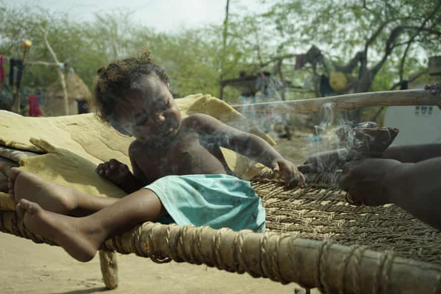 A traditional healer wafts smoke over a baby aged around one year old.