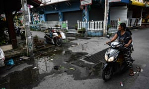 A woman drives by the aftermath of the double bomb attack in Hua Hin.